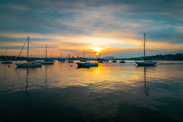 Boats_on_still_water_morning_clouds stock photo