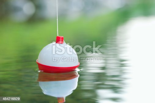 A red and white bobber floats on water with ripples