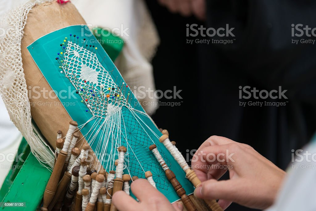 bobbin lacemaking - white lace with colorful needles stock photo