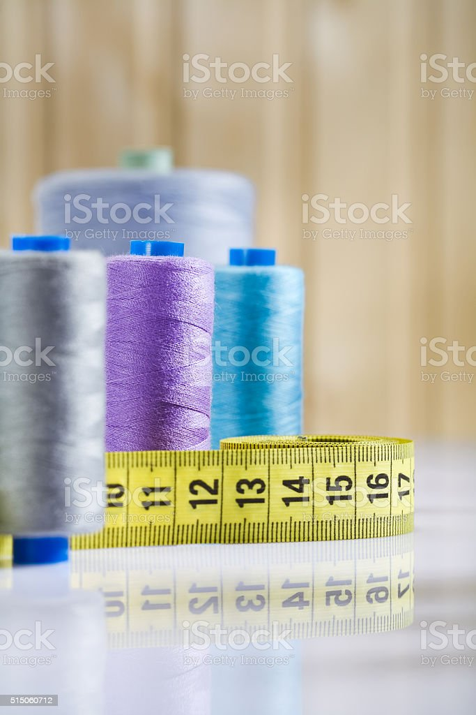 bobbins and measure tape on table stock photo