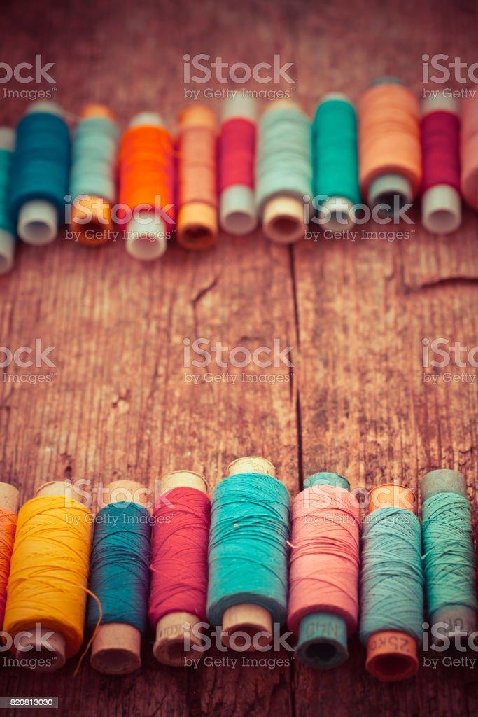 Bobinas com fios coloridos na velha mesa de madeira plano de fundo, fundo de costura - foto de acervo