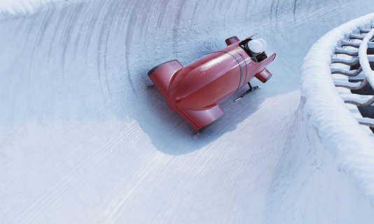Bobsleigh team is riding on a high speed in a turn