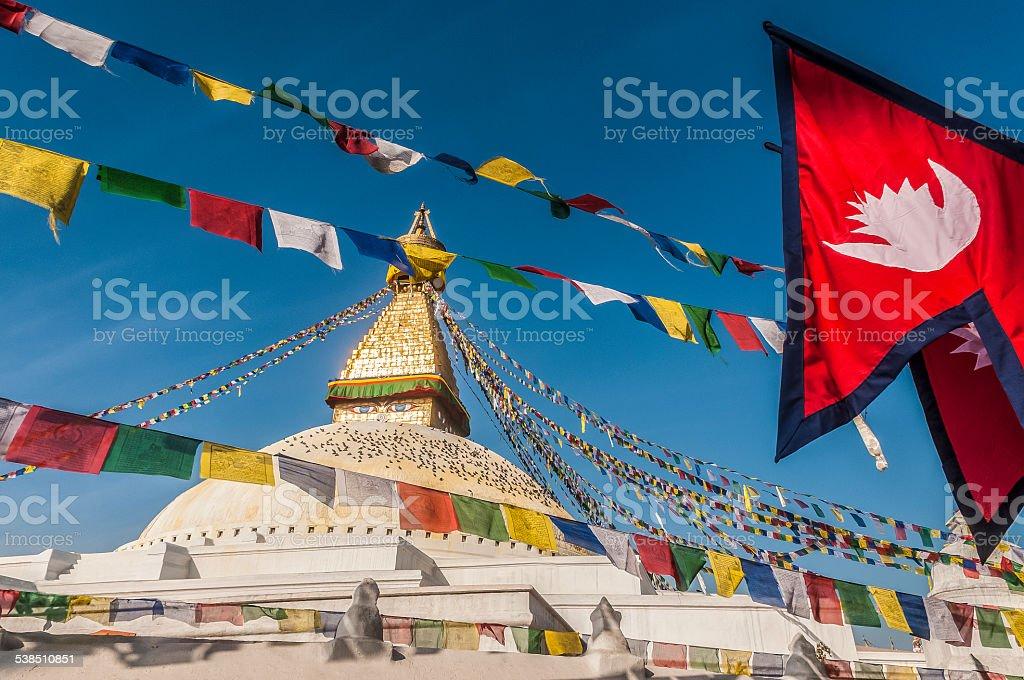 Bodhnath Stupa with Prayer Flags and Nepalese Flag, Kathmandu, Nepal stock photo