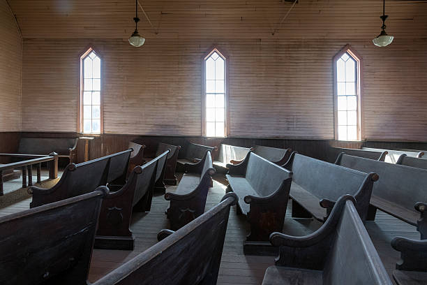 """Bodie Ghost Town Methodist Church Interior Interior of the Methodist Church in Bodie, California, a ghost town maintained as the Bodie State Historic Park.  It is also recognized as the Bodie Historic District by the US Department of the Interior.  It is maintained in a state of """"arrested decay"""" by the nonprofit Bodie Foundation. The town began after a gold strike in 1859, reached its peak population of 5,000-7,000 in 1879, but declined to 120 persons by 1912.  In 1962, the remaining landowner sold the town to the state of California.  Bodie is located in Mono County 12 miles southeast of the town of Bridgeport at an elevation of 8379 feet (2554 m). pew stock pictures, royalty-free photos & images"""