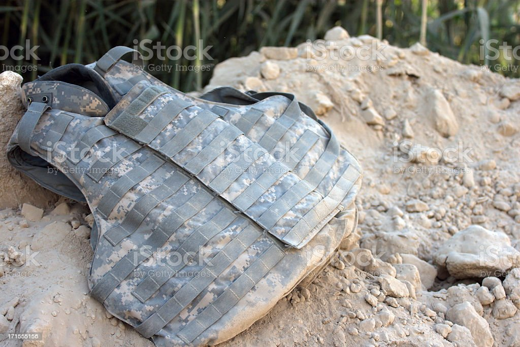 Body armor vest laying on a pile of dirt stock photo