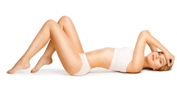 body beauty, slim woman in cotton underwear lying down on back, happy dreaming girl white isolated - the human body stock pictures, royalty-free photos & images