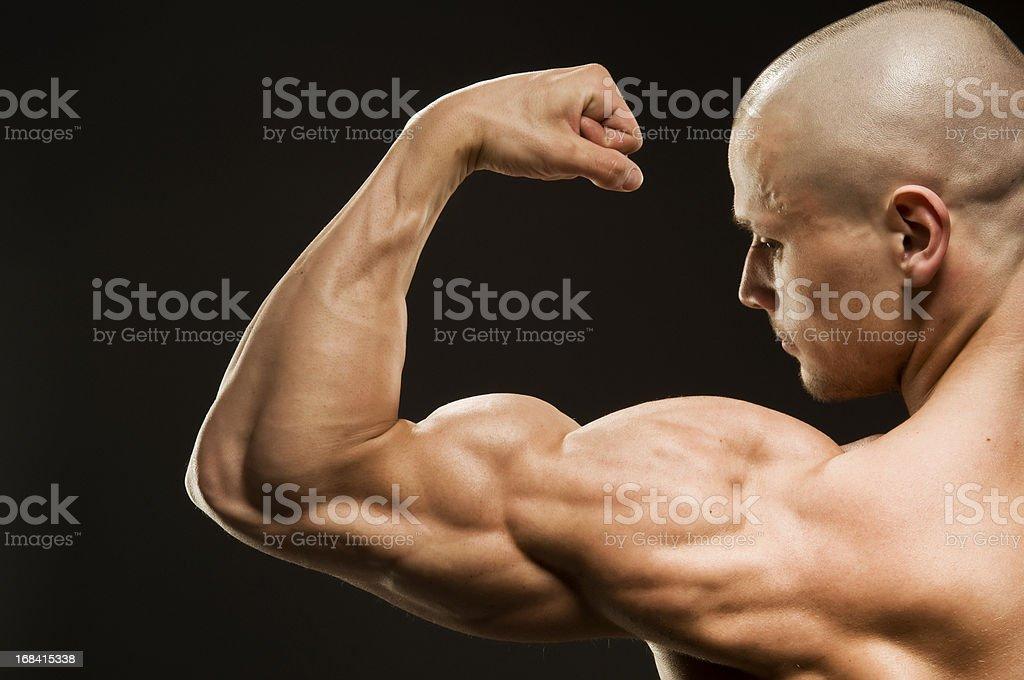 Body builder flexing biceps on black background royalty-free stock photo