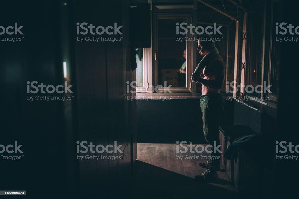 One man, fit shirtless man standing in dark locker room in gym alone.