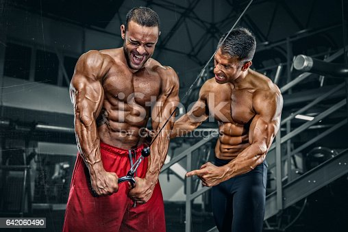 Two Muscular Men exercise at the gym