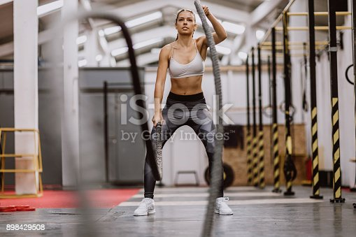 Woman Losing Weight Using Battle Ropes In Gym