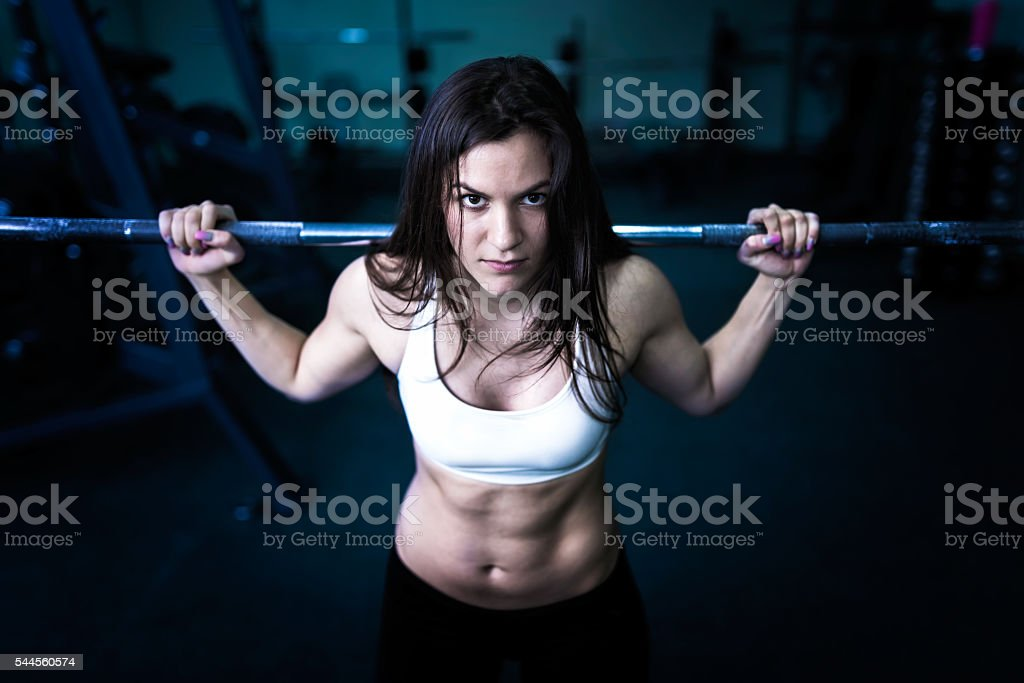 Body Building Girl Lifting Weights in Gym stock photo