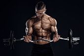 Athletic Men performing barbell biceps curls. Studio Shot. Copy Space