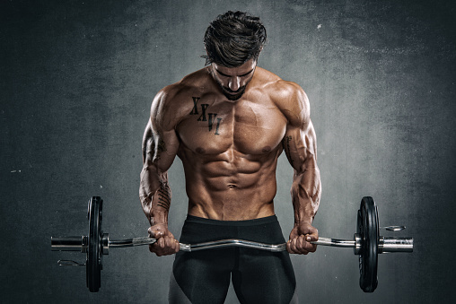 Muscular Men Exercise With Weights. He is performing barbell biceps curls