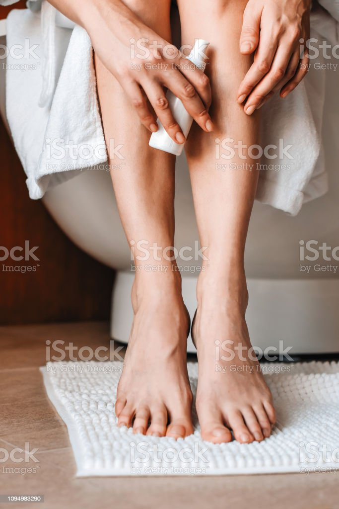 Body care. A young woman in the bathroom applies natural cream to her legs. Cosmetics and anti-cellulite care - foto stock