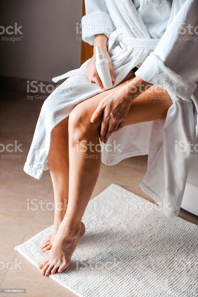 Body care. A young woman in the bathroom applies natural cream to her legs. Anti-cellulite care - foto stock