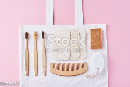 1169442288 istock photo Body care natural wooden eco friendly products on a pink background, flat lay top view. Bamboo toothbrushes, wooden comb, soap, spongle and natural washclothers. Zero waste concept 1177808424
