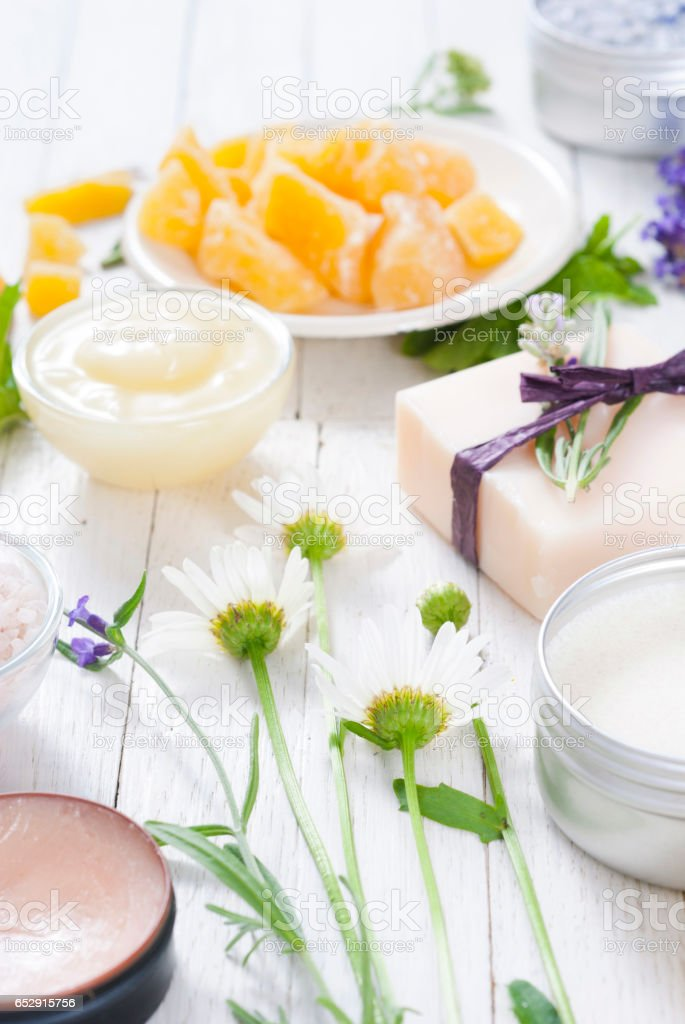 cosmetic creams, lip balm, soap and bath salt with herbal flowers on...
