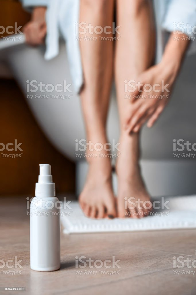 Body care. Young woman in the bathroom stroking her legs. Cosmetics for care and anti-cellulite in the foreground. - foto stock