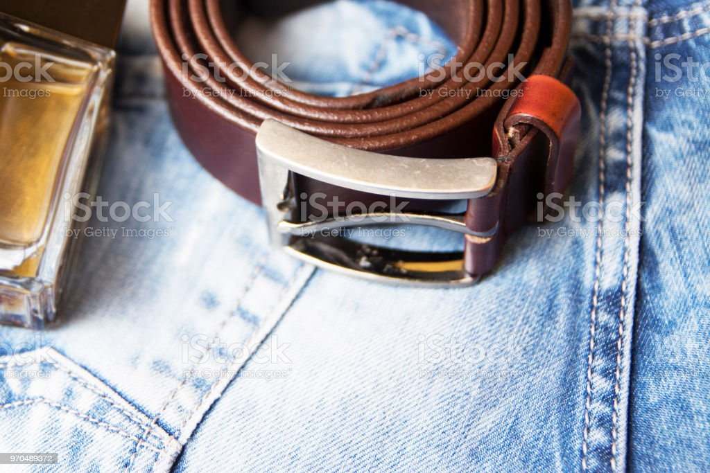 Body Care,perfume and belt on top of jeans pants stock photo