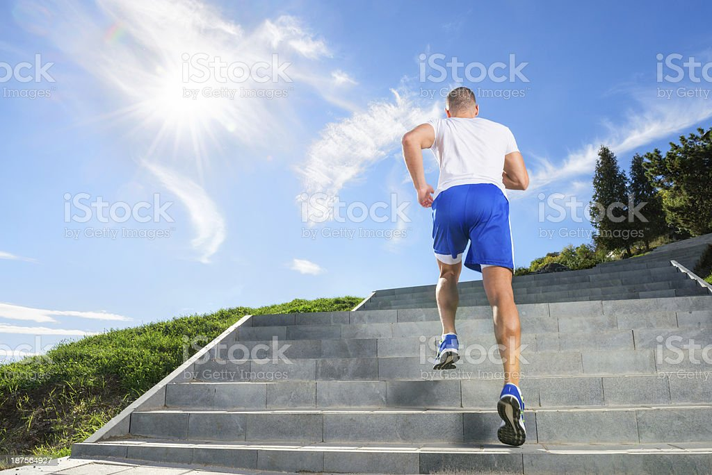 Athlete staying motivated and exercising on stairs in a sunny day