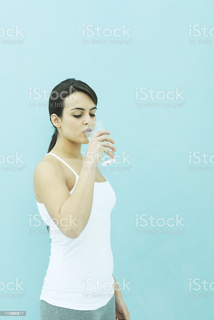 Healthy woman drinking water after gym training.
