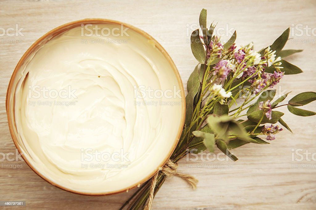 body cream and wildflowers on wooden table stock photo