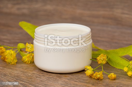 istock body cream opened plastic jar with chamomile and linden flowers on wooden table 1127557382