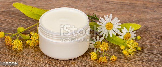 istock body cream opened plastic jar with chamomile and linden flowers on wooden table 1127557394