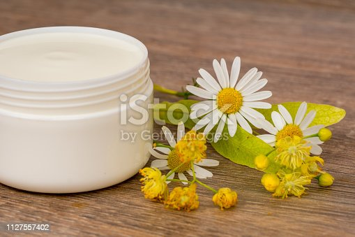 istock body cream opened plastic jar with chamomile and linden flowers on wooden table 1127557402