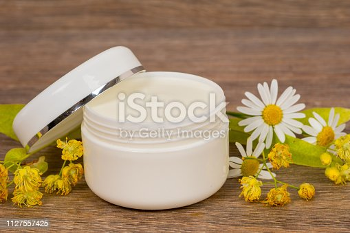 istock body cream opened plastic jar with chamomile and linden flowers on wooden table 1127557425