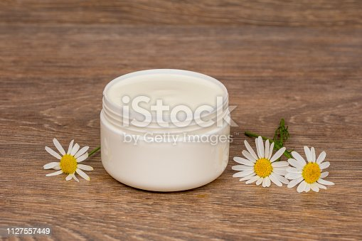 istock body cream opened plastic jar with chamomile flowers on wooden table 1127557449