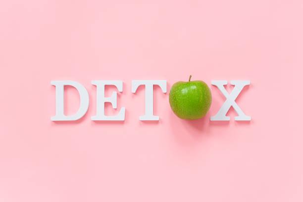 detoksykacji ciała i zdrowej diety koncepcji. zielone naturalne świeże jabłko w słowie detox z białych liter na różowym tle. kreatywny płaski lay widok z góry przestrzeń kopiowania - detoks zdjęcia i obrazy z banku zdjęć