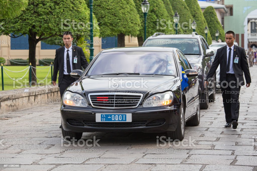 Body guards protect state automobile, which moves in the Grand Palace in Bangkok. stock photo