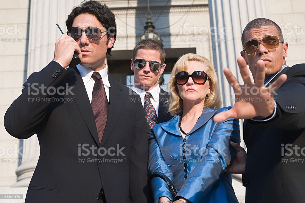 Body guards protecting a woman royalty-free stock photo