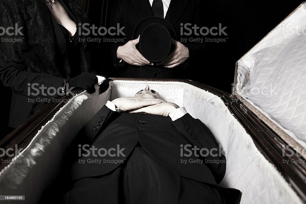 Body in a coffin with grieving widow and pallbearer stock photo