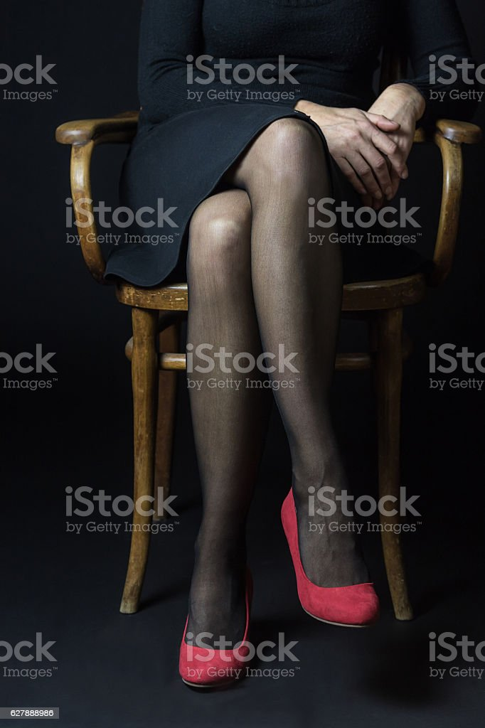 Body language - Woman is sitting with legs crossed stock photo