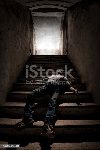 A dead body lying on the dark stairs of a cellar.