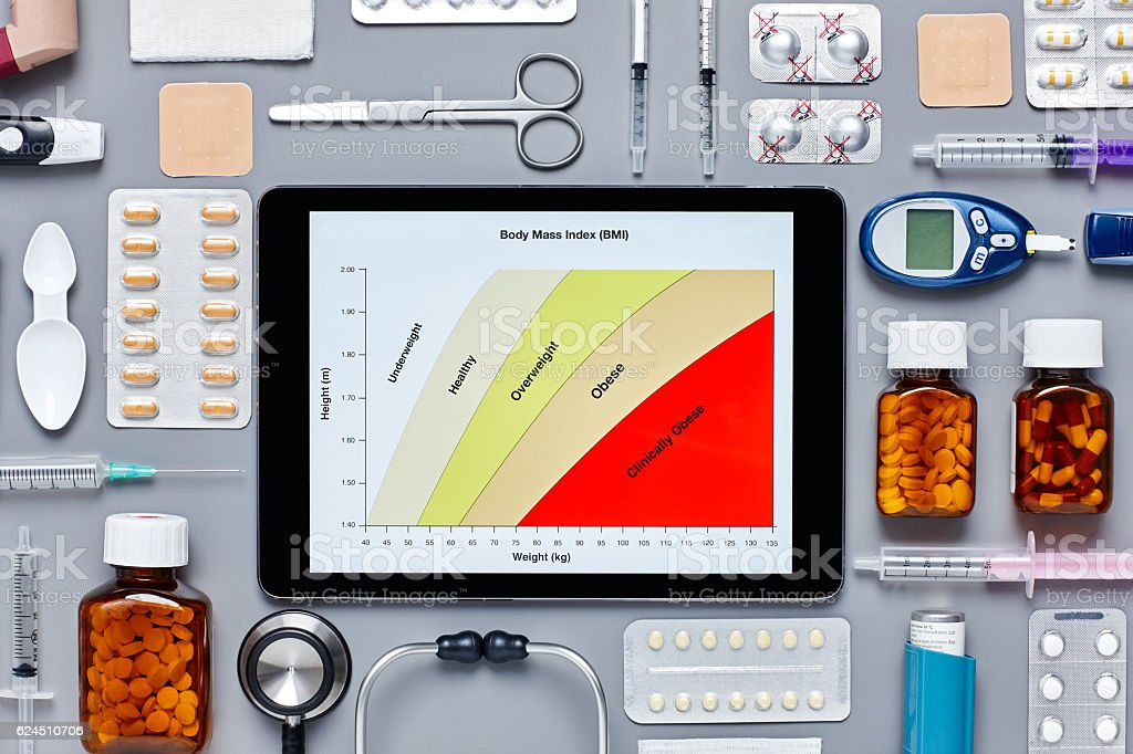 Body mass index displayed on digital tablet amidst medical equip stock photo