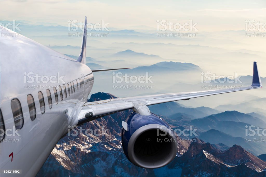 Body of an Airplane Flying Above Cloud at dusk stock photo