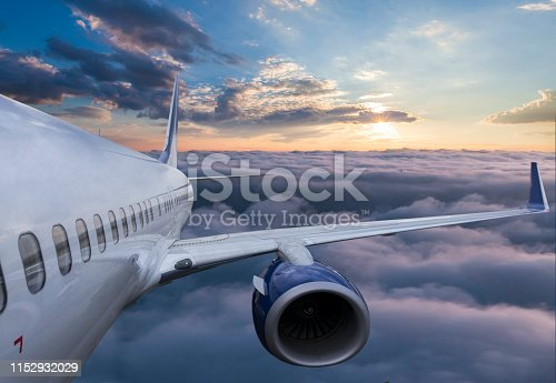 Body of an Airplane Flying Through Clouds at sunset