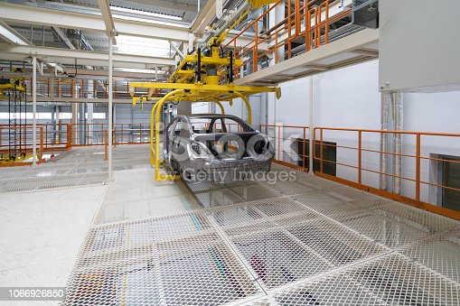 1069360792 istock photo body of car on conveyor Modern Assembly of cars at plant. automated build process of the car body 1066926850