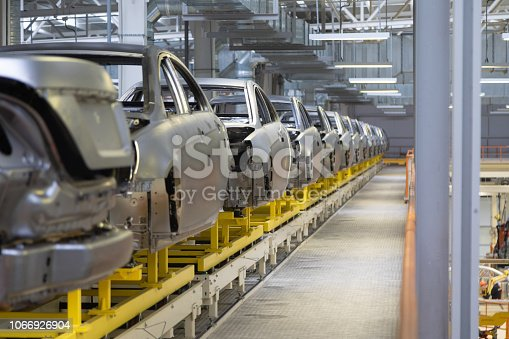 1069360792 istock photo body of car on conveyor Modern Assembly of cars at plant. automated build process of car body 1066926904