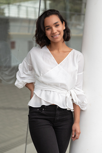 body of young Latin brunette woman and black hair, standing and smiling, wearing a white blouse and black pants, photo in the day