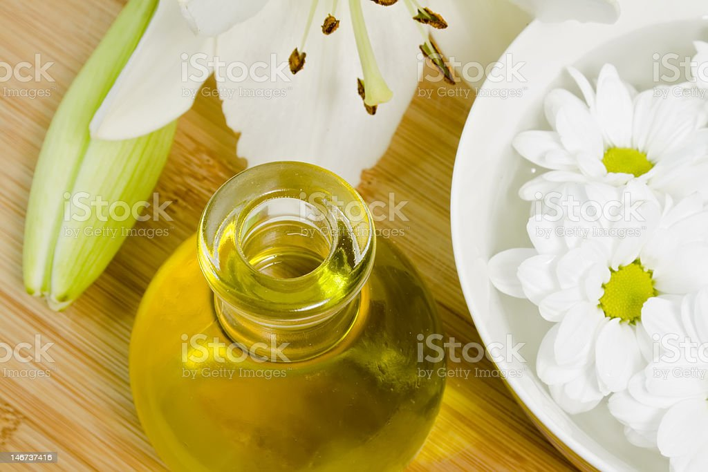 body oil and daisy flowers in a bowl of water royalty-free stock photo
