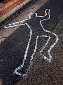 Painted outline of a person's body on bitumen / asphalt road