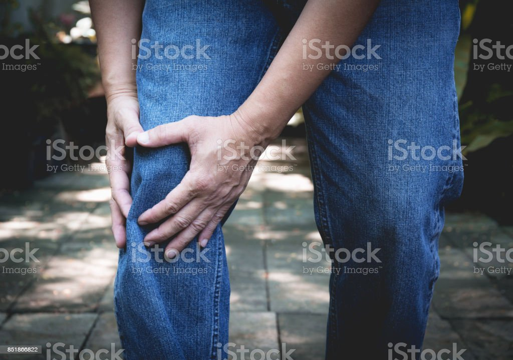 Body pain. close-up male body with pain in knees. Man hands touching and massaging painful knee. stock photo