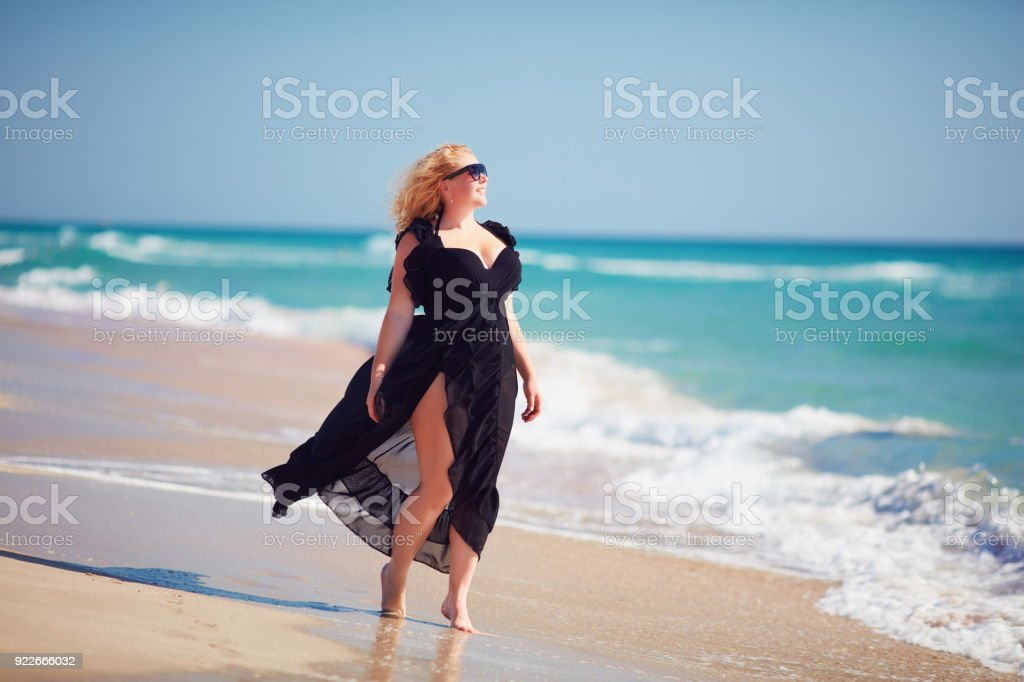 body positive, plus size woman enjoys summer day at the beach stock photo