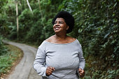 istock Body positive woman running in nature park 1264830311
