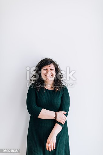 Body positive young female standing, smiling and looking at camera
