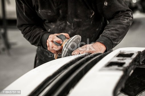 Car repair technician using a pneumatic sanding tool to remove excess filling form a car number that got damaged in accident.